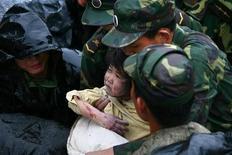 <p>Immagine d'archivio del salvataggio di una bimba in occasione del terremoto dello scorso anno in Cina. REUTERS/Bo Bor (CHINA)</p>
