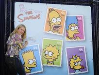 """<p>Nancy Cartwright, a voz de Bart Simpson, assina um poster da inauguração dos novos selos postais de """"Os Simpsons"""" em Los Angeles. 07/05/2009. REUTERS/Phil McCarten</p>"""