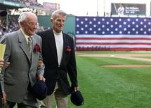 <p>Dom Dimaggio (L) and Johnny Pesky take to the field arm in arm at Boston's Fenway Park to honor Ted Williams July 22, 2002. REUTERS/Jim Bourg</p>