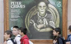 """<p>Foto del 1 de mayo de escolares caminando frente a un cartel pegado en el London Coliseum promocionando la próxima producción de la ópera Peter Grimes"""", del autor británico Benjamin Britten. Algunas personas visitan la localidad de Aldeburgh, sobre la pedregosa costa este de Inglaterra, para ver el lugar donde el autor Benjamin Britten ambientó su desgarradora ópera de venganza colectiva """"Peter Grimes"""". REUTERS/Simon Newman (GRAN BRETAÑA)</p>"""