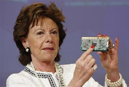 European Commissioner for Competition Neelie Kroes shows a computer chip at a news conference on Intel at the European Commission headquarters in Brussels, May 13, 2009. REUTERS/Thierry Roge