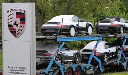 A car transporter loaded with Porsche vehicles passes a Porsche logo in front of the Porsche Development Center in Weissach near Stuttgart May 18, 2009. Volkswagen. REUTERS/Johannes Eisele