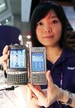 <p>Immagine d'archivio di una venditrice che mostra due smartphone. REUTERS/Richard Chung</p>