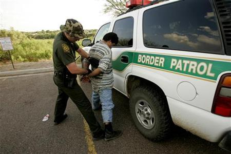 Border Patrol Agent Luis Garza (L) searches an undocumented immigrant from Mexico he detained, after the man was caught coming into Laredo, Texas from Mexico (in the background), May 1, 2006. REUTERS/Rick Wilking
