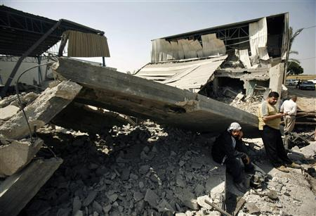 Palestinians rest next to a metal workshop that was destroyed after an Israeli air strike in Gaza City May 20, 2009. REUTERS/Suhaib Salem