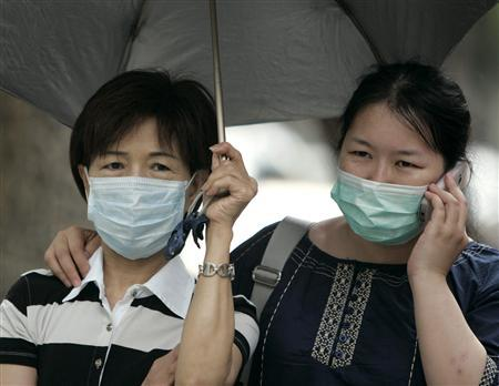 People wear medical masks while walking past a hospital in Taipei May 22, 2009. REUTERS/Pichi Chuang