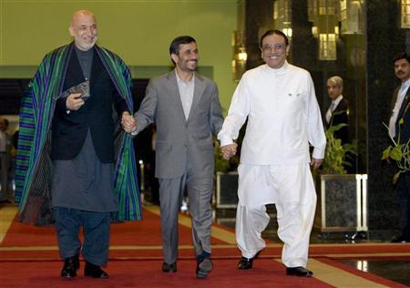 Presidents Hamid Karzai of Afghanistan, Mahmoud Ahmadinejad of Iran and Asif Ali Zardari of Pakistan (L-R) hold hands as they walk to the conference room to begin their trilateral summit in Tehran May 24, 2009. The presidents of Iran, Afghanistan and Pakistan began talks in Tehran on Sunday on ways to combat terrorism, drug trafficking and other regional security problems. REUTERS/Raheb Homavandi (IRAN POLITICS)