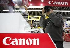 <p>Un hombre prueba una cámara digital Canon en una tienda en Tokio, 30 abr 2009. La japonesa Canon Inc dijo el lunes que el negocio marchó mejor de lo esperado en los últimos meses y que los planes de estímulo de Gobiernos alrededor del mundo están comenzando a rendir frutos. REUTERS/Yuriko Nakao/Archivo</p>