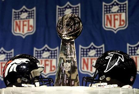 The Vince Lombardi Trophy is flanked by team helmets from the Denver Broncos (L) and Atlanta Falcons (R) while on display in Miami January 29, 1999. REUTERS/Mike Segar