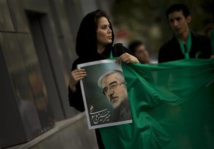 A supporter carrying a picture of Mirhossein Mousavi, former Iranian Prime Minister and presidential candidate, as she holds a green cloth, the symbolic colour of Mousavi's campaign, in Tehran, May 25, 2009. REUTERS/Morteza Nikoubazl (IRAN POLITICS ELECTIONS IMAGES OF THE DAY)