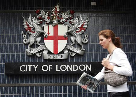 A pedestrian walks past the City of London emblem on Queen Victoria street in central London July 8, 2005. REUTERS/Pascal Rossignol PR/ABP/PN