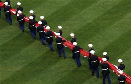 U.S. Marines carry the American flag across the outfield before pre-game ceremonies for the New York Mets' home opener against the San Diego Padres at Citi Field in New York, April 13, 2009. REUTERS/Mike Segar