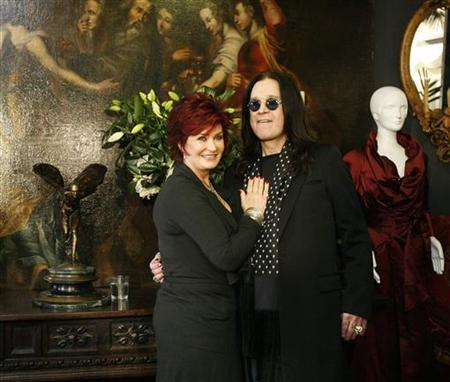 Ozzy and Sharon Osbourne pose in front of some of their belongings to be auctioned in Beverly Hills, California, November 26, 2007. REUTERS/Mario Anzuoni