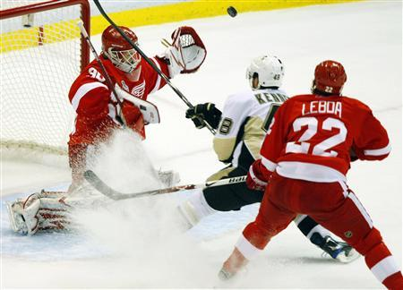 Detroit Red Wings' Chris Osgood (L) makes a save on Pittsburgh Penguins' Tyler Kennedy while Red Wings' Brett Lebda (R) watches during the first period in Game 1 of the NHL Stanley Cup Final hockey series in Detroit, Michigan May 30, 2009. REUTERS/Rebecca Cook
