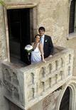 <p>Лука Чекаррели (справа) и его невеста Ирэн Лафронти позируют для фотографов на балконе Джульетты в Вероне 1 июня 2009 года. Современные Ромео наконец-то обручились со своими Джульеттами, поскольку в понедельник в городе Верона, расположенном на севере Италии, для проведения свадеб открылся тот самый балкон, на котором героиня пьесы Уильяма Шекспира дожидалась своего возлюбленного. REUTERS/Alessandro Garofalo</p>