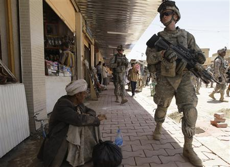 A U.S. soldier walks past a man during a patrol in Samarra, north of Baghdad, June 2, 2009. REUTERS/Mohammed Ameen