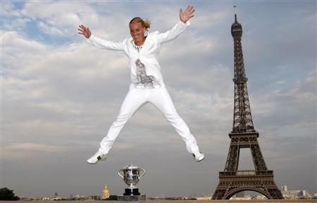 Russia's Svetlana Kuznetsova poses for photographers with a jump beside her trophy near the Eiffel Tower in Paris, after defeating her compatriot Dinara Safina in the women's final at the French Open tennis tournament at Roland Garros June 6, 2009. REUTERS/Vincent Kessler
