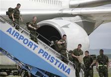 <p>Британские солдаты выходят спускаются по трапу самолета в аэропорту Приштины 24 мая 2008 года. НАТО планирует сократить численность своего миротворческого контингента в Косово до 10.000 человек с нынешних 15.000 к январю следующего года, сказал в понедельник высокопоставленный представитель США. REUTERS/Hazir Reka</p>
