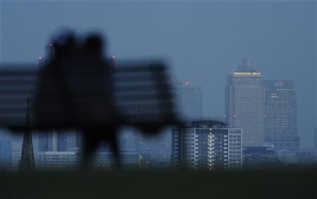 A couple embrace, as the Canary Wharf financial district is seen behind, in London January 22, 2009. REUTERS/Toby Melville