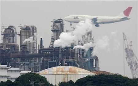 An airplane flies near emissions from a factory at Keihin industrial zone in Kawasaki, south of Tokyo in this November 12, 2008 file photo. REUTERS/Toru Hanai