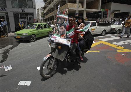 A supporter of Iranian presidential candidate Mahmoud Ahmadinejad rides his motorcycle with the windshield covered with campaign posters during a rally in front of Tehran's Sharif University June 10, 2009. REUTERS/Ahmed Jadallah