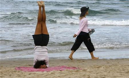 A woman practises a headstand on a beach in Tel Aviv April 30, 2008. REUTERS/Gil Cohen Magen
