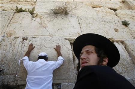 A Jewish worshipper prays as an ultra-Orthodox Jew sits in front of the Western Wall, Judaism's holiest prayer site, in Jerusalem's Old City May 28, 2009. REUTERS/Baz Ratner