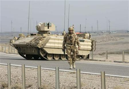 A British soldier secures a road outside Basra's airport, where the handover ceremony is held, December 16, 2007. REUTERS/Atef Hassan
