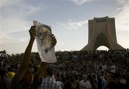 A demonstrator shows a picture of former presidential candidate Mirhossein Mousavi during a rally in support of Mousavi in western Tehran June 15, 2009. REUTERS/Caren Firouz