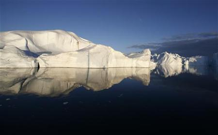 Icebergs are reflected in the calm waters at the mouth of the Jakobshavn ice fjord near Ilulissat in Greenland in this photo taken May 15, 2007. REUTERS/Bob Strong/Files