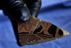 <p>Immagine d'archivio di un reperto archeologico mostrato da un carabiniere. REUTERS</p>