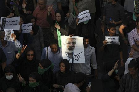 EDITORS' NOTE: Reuters and other foreign media are subject to Iranian restrictions on leaving the office to report, film or take pictures in Tehran Protesters hold signs and a picture of defeated reformist presidential candidate Mirhossein Mousavi during a silent demonstration against the results of the Iranian presidential election in central Tehran June 17, 2009. Picture taken June 17, 2009. REUTERS/Fars News