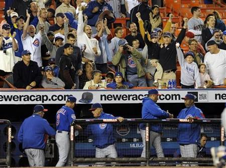 Chicago Cubs fans behind the visiting dugout celebrate with their team after they beat the New York Mets in their MLB National League game in New York September 22, 2008. REUTERS/Ray Stubblebine