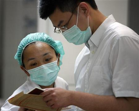 Medical staff work near a quarantine area where a man is held for having the H1N1 flu at Taoyuan General Hospital, northern Taiwan, May 20, 2009. REUTERS/Nicky Loh