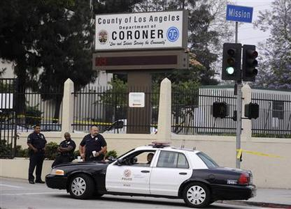 Los Angeles Police Department officers are stationed at the entrance of the County of Los Angeles Department of Coroner facility June 26, 2009. REUTERS/Phil McCarten