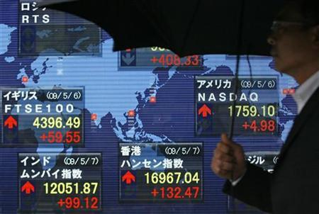 A man walks past a board displaying stock indexes around the world in Tokyo May 7, 2009. REUTERS/Michael Caronna