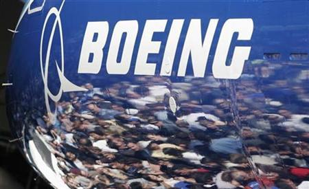 Invited guests for the world premiere of the Boeing 787 Dreamliner are reflected in the fuselage of the aircraft at the 787 assembly plant in Everett, Washington, July 8, 2007. REUTERS/Robert Sorbo (UNITED STATES)