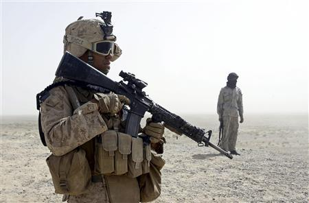 A U.S. Marine from 5th Battalion 10th Marines patrols with a member of an Afghan border guard unit in the desert of the lower Helmand River valley, in southern Afghanistan July 1, 2009. REUTERS/ Peter Graff