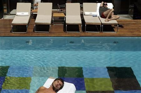 Hotel guests sunbathe at the pool of the Axel Hotel in Buenos Aires November 1, 2007. REUTERS/Marcos Brindicci