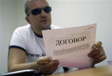 <p>Viktor Mirosiichenko, the public face of Kontora loan company, shows a contract with a borrower at his office in Riga July 2, 2009. REUTERS/Ints Kalnins</p>