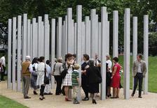 <p>Amici e parenti delle vittime degli attentati del 7 luglio 2005 a Londra camminano tra le colonne del London Bombing Memorial prima della sua presentazione ad Hyde Park. REUTERS/Stephen Hird (BRITAIN ANNIVERSARY POLITICS)</p>