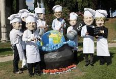 <p>Gli attivisti dell'Ong Oxfam nell'azione dimostrativa di oggi a Roma con le maschere dei leader G8 vestiti da cuochi. REUTERS/Remo Casilli</p>