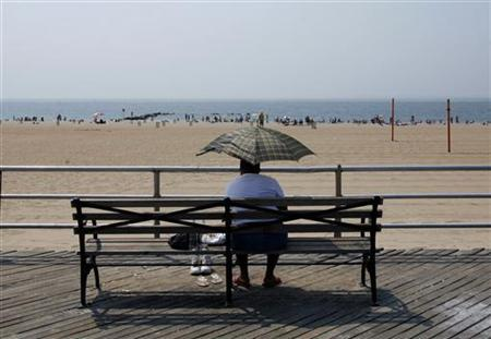 A woman takes shelter under an umbrella as she sits on a boardwalk bench on Coney Island in the Brooklyn Section of New York City August 3, 2007. REUTERS/Mike Segar