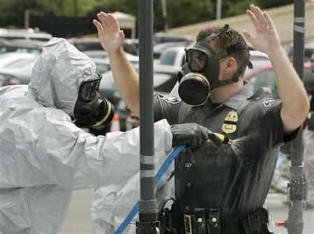 A Pentagon Force Protection Agency (PFPA) police officer is washed down after a simulated infection of anthrax during a full-scale bio-exercise drill outside the Pentagon in 2006. REUTERS/Jim Young