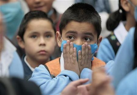 A child wearing a surgical mask as protection against influenza A (H1N1) attends class in Mexico City May 11, 2009. REUTERS/Henry Romero