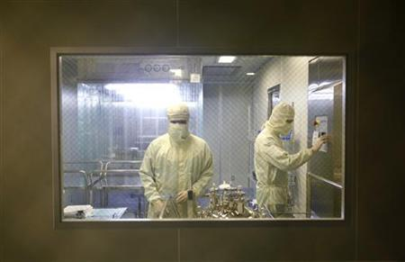 Men in medical suits work inside the AdImmune flu vaccine manufacturing facility in Taichung June 18, 2009. REUTERS/Nicky Loh