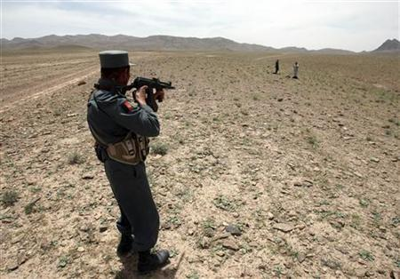 An Afghan policeman points his rifle at two Afghan men in the Golestan district of Farah province May 8, 2009. REUTERS/Goran Tomasevic