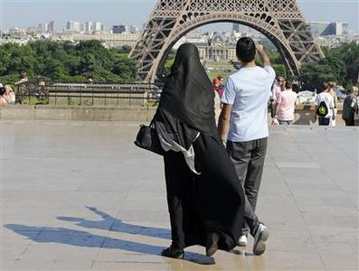 File photo of a woman wearing a niqab walks at Trocadero square near the Eiffel Tower in Paris June 24, 2009. REUTERS/Gonzalo Fuentes/Files