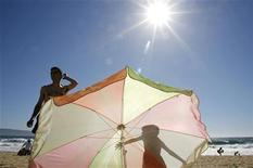 <p>A boy casts a shadow on a sunshade as he stands next to his father on a beach in Vina del Mar city, 85 miles (137 km) northwest of Santiago, December 28, 2006. REUTERS/Eliseo Fernandez</p>