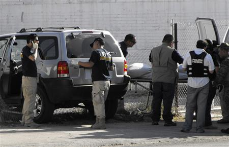 Forensic experts remove a body from a vehicle in the border city of Ciudad Juarez, July 14, 2009. REUTERS/Alejandro Bringas